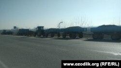 Груженные навозом тракторы стоят на трассе при въезде из Джизака в Самаркандскую область, 11 января 2021 года.