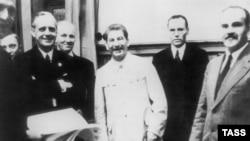 У 1939 році 23 серпня в Москві був підписаний Договір про ненапад. Документ підписали міністри закордонних справ Німеччини Ріббентроп (ліворуч) та СРСР Молотов (праворуч). Сталін (у центрі) підкреслив своєю присутністю важливість підписання договору