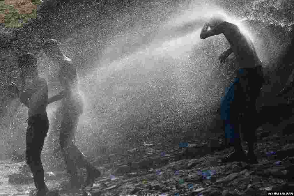 Karachi residents cool off as water sprays from a pipeline during a hot summer's day in a slum area of the Pakistani city on July 2. (AFP/Asif Hassan)