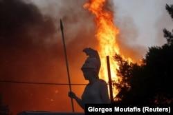 Athéné istennő szobra, a háttérben Varimpompi lángol, Athéntól északra, 2021. augusztus 3-án
