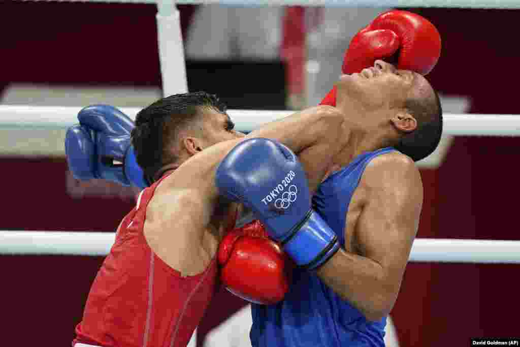 Daniyal Shahbakhsh, of the Islamic Republic of Iran, exchanges punches with Morocco's Mohamed Hamout during their men's featherweight 57-kg boxing match at the 2020 Summer Olympics, Saturday, July 24, 2021, in Tokyo, Japan.