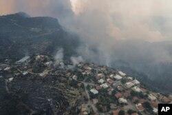 O vedere aeriană a satului Sirtkoy, cuprins de flăcări, în apropierea localității Manavgat. Peste 100 de incendii au fost aduse sub control în Turcia, potrivit oficialilor.