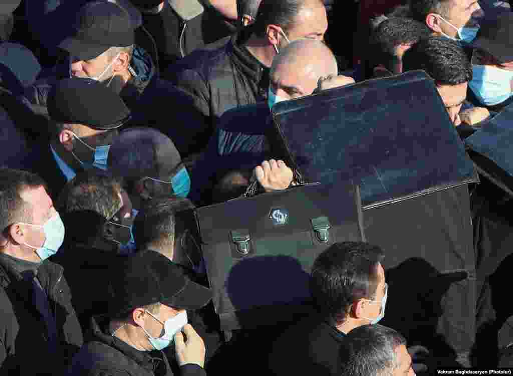 Телохранители го чуваат ерменскиот премиер Никол Пашинијан додека влегува на гробиштата во Јераблур на 19 декември.