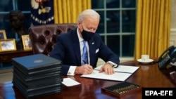 Джо Байден во время своих первых минут в качестве президента в Овальном кабинете. Вашингтон, 20 января 2020 года.