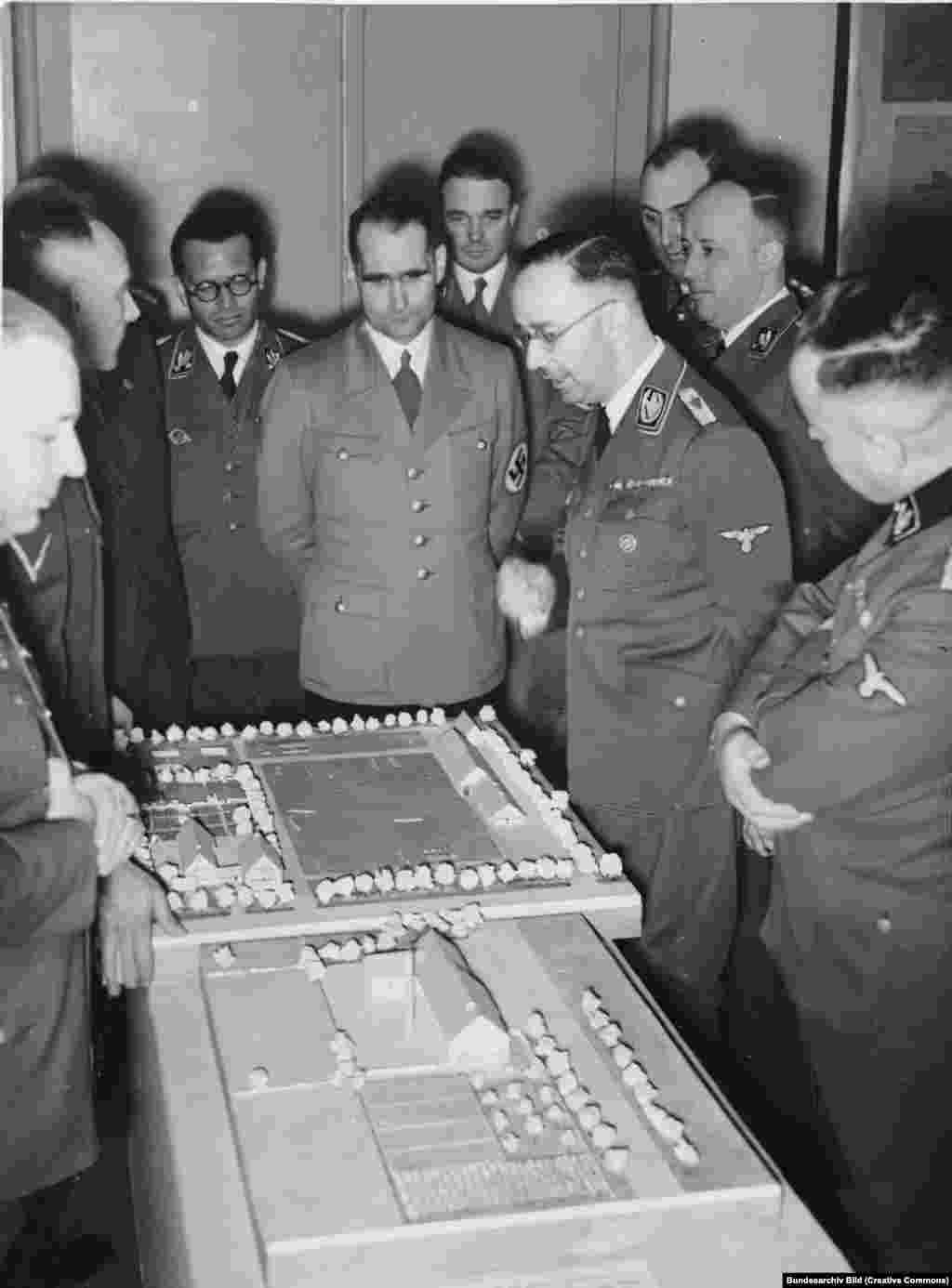 """Генрих Гиммлер и другие высокопоставленные нацисты рассматривают план создания поселений этнических немцев на советской территории в марте 1941 года. Вторжение готовилось годами, и на него намекал в манифесте «Майн Кампф» 1925 года нацистский лидер Адольф Гитлер, когда писал: «Если мы говорим о новой земле и территории в сегодняшней Европе, в первую очередь на ум приходят только Россия и ее страны-вассалы""""."""