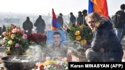 Egy nő lerója a tiszteletét a karabahi háború egy áldozata előtt egy a Jerablur Katonai Sírkertben tartott meglékezésen, Jerevánban, Örményországban. 2020. december 19.
