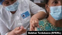 Женщина получает вакцину против COVID-19 в одной из поликлиник Бишкека. Май 2021 года.