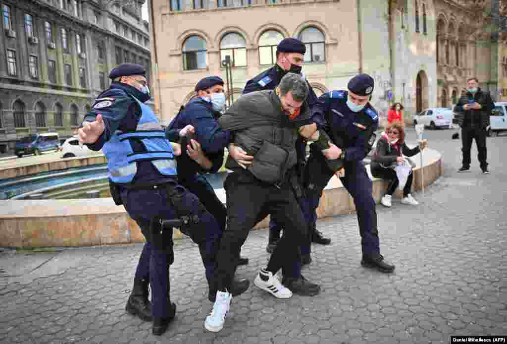 Romanian police officers struggle to detain a man.Around 2,000 people took part in a protest and march in downtown Bucharest, claiming that the restrictions limit their civil rights.