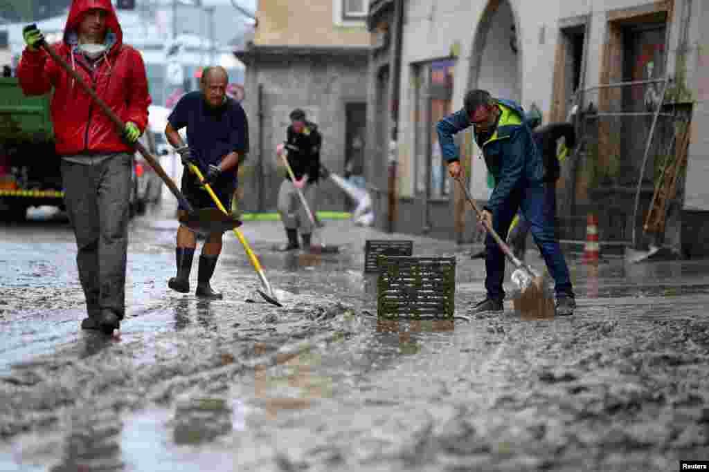 Ljudi uklanjaju blato nakon poplave u centru grada Hallein, Austrija, 18. jula 2021.