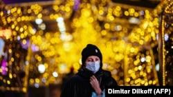 Женщина в маске под новогодними украшениями. Москва, 15 декабря 2020 года.