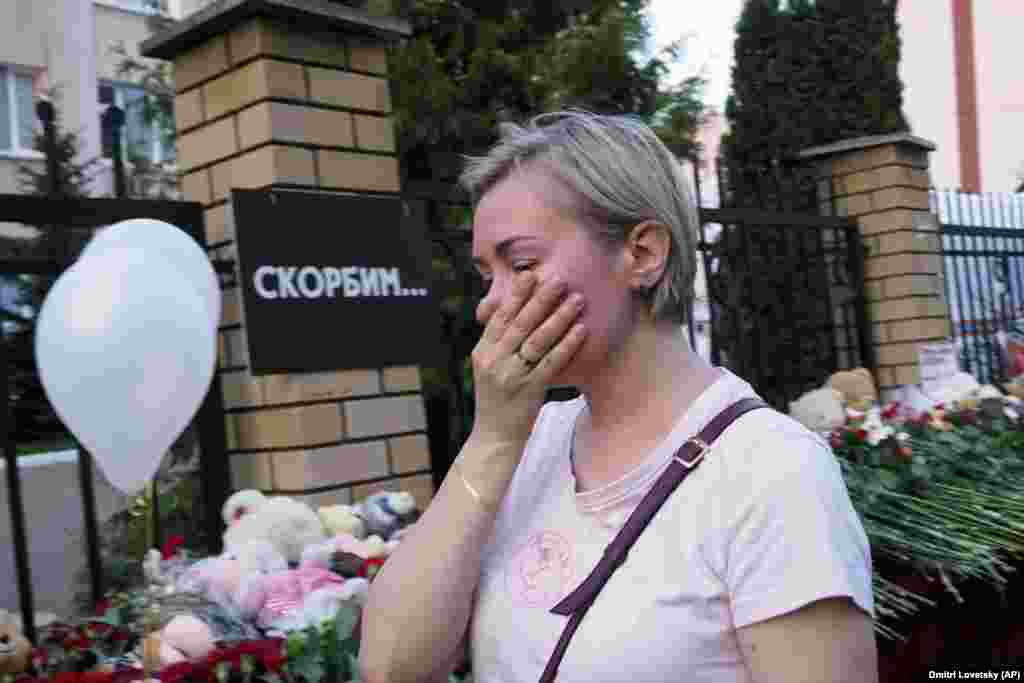 """A woman cries near a school in Kazan on May 11. The writing on the wall reads, """"We grieve."""""""