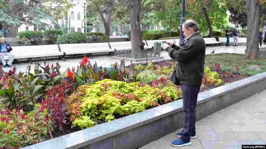 На Пушкінському бульварі хтось поспішає сфотографувати осінні квіти