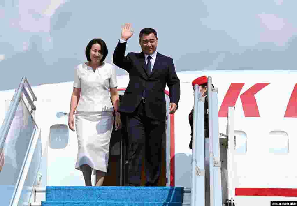 Президент Садыр Жапаров жана анын жубайы, биринчи канайым Айгүл Асанбаева учактан түшүп баратышат.