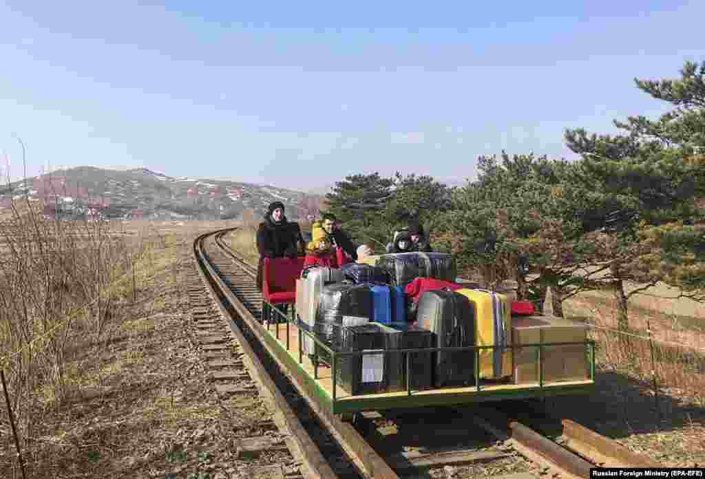 Russian diplomats and family members leave North Korea and head home to Russia using a hand-pushed rail trolley due to Pyongyang's coronavirus restrictions, near Khasan, in the Primorye region. (epa-EFE)