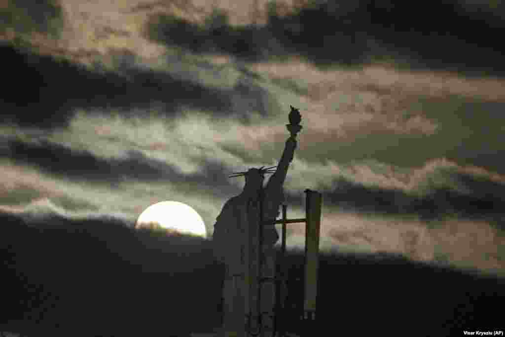 The moon rises over a replica of the Statue of Liberty in the Kosovar capital, Pristina. (AP/Visar Kryeziu)