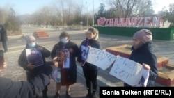 Слева направо: жительницы города Жанаозена Аманбике Егизбаева, Зияда Отебекова, Жанар Сагинова и Гульжахан Табылдиева возле городской площади c портретами родных, содержащихся под стражей, и плакатом с призывом к справедливости. Жанаозен, 17 декабря 2020 года.