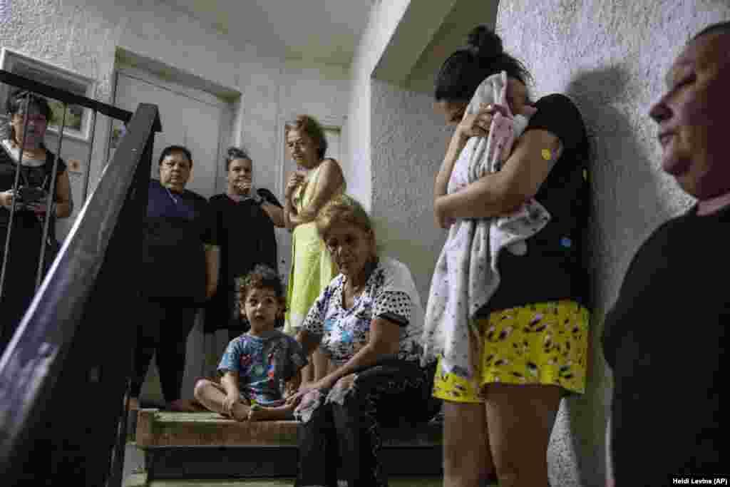 Ізраїльтяни ховаються на сходовій площадці свого багатоквартирного будинку, коли звучить сирена, що попереджає про наближення ракет, випущених зі Смуги Гази, в Ашдоді, Ізраїль. 19 травня 2021 року