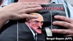 """Un protestat ține un portret al președintelui Lukașenko cu mesajul """"Opriți criminalul"""" în timp ce strânge semnături pentru opoziție"""