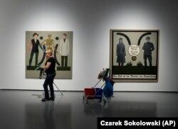 """Takarítónő Hornsleth művei előtt az Ujazdowski Kastély Kortárs Művészeti Központban. A jobb oldali képen a felirat: """"Német anyák, német apák, a halál mester Németországból"""". Varsó, 2021. augusztus 25-én"""