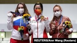 Кытайлык ок атуучу, алтын байгенин ээси Цянь Ян (ортодо) орусиялык Анастасия Галаш (солдо) жана швейцариялык Нина Кристен (оңдо) сыйлоо аземи учурунда. Токио. 24-июль, 2021-жыл.