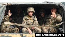 NAGORNO-KARABAKH -- Servicemen of Karabakh's Defence Army wave while riding in the back of a truck on the way to the town of Martakert, September 29, 2020.