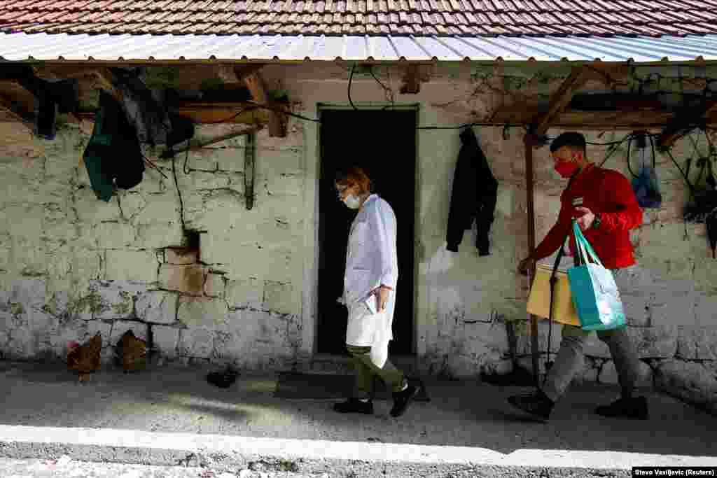 Медичний працівник та волонтер Червоного Хреста йдуть вакцинувати наступного селянина
