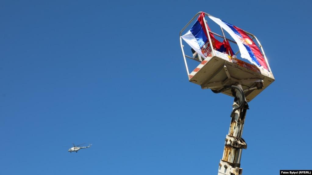 Një helikopter i NATO-s duke fluturuar, pranë një flamuri të Serbisë, në Jarinjë. (26 shtator)