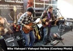 Chitaristul Joe Berger (dreapta) testează o chitară marca Vlahopol Guitars la târgul NAMM de la Los Angeles.