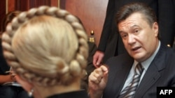Viktor Yanukovych, who later went on to defeat Yulia Tymoshenko in the 2010 presidential election, speaks with her during talks in Kyiv in 2007.