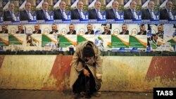Старушка просит милостыню на фоне развешанных на стене постеров кандидатов в президенты. Тбилиси, 25 октября 2013 года.
