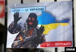 Плакат с изображением президента России Владимира Путина во время акции «Крым – это Украина» у российского посольства в Киеве, 16 марта 2020 года