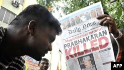 A Sri Lankan man holds a newspaper that details the end of the near four-decades long ethnic conflict.