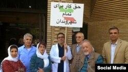 قاسم اکسیری فرد (وسط با پلاکاردی در دست) در حال اعتراض مقابل دانشگاه خواجه نصیر