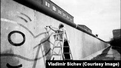 Американский художник Кит Харинг рисует на западной стороне Берлинской стены, 1986 год.