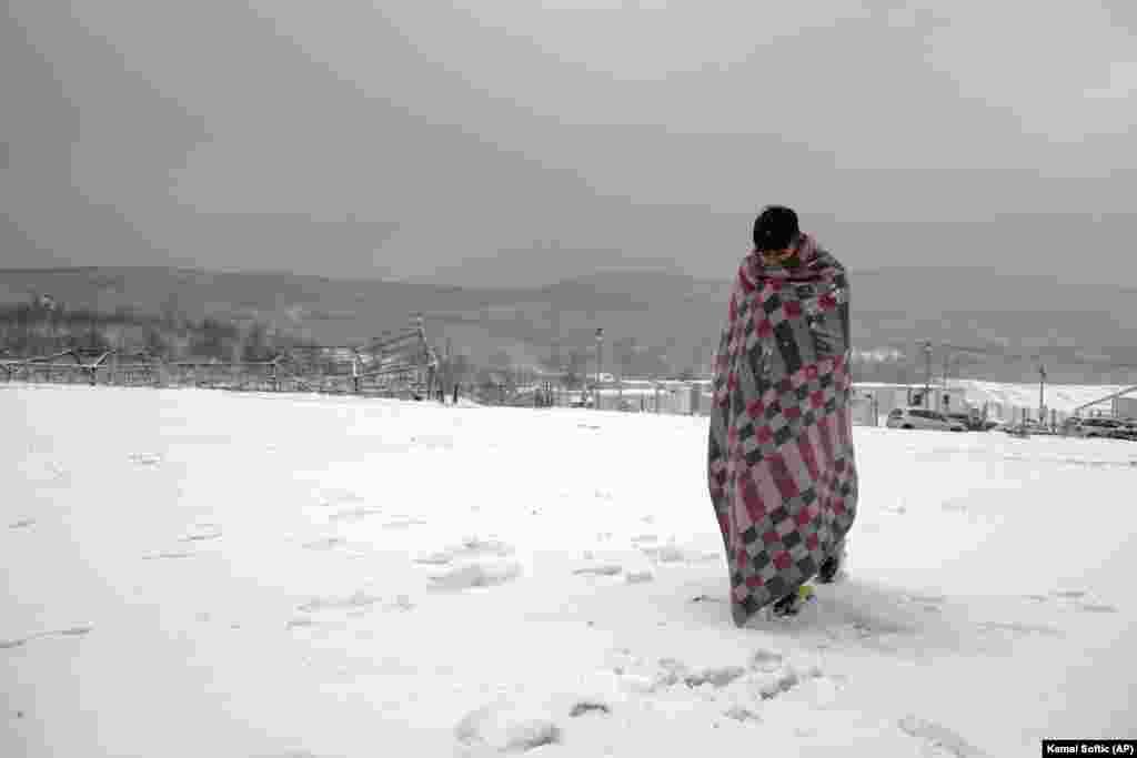 Egy takaróval a hátán sétál a hóban ez a menekült a boszniai Lipa menekülttáborban december 26-án.