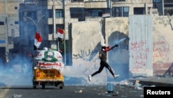 A demonstrator throws away a tear gas canister during an anti-government protest in Baghdad on November 1.