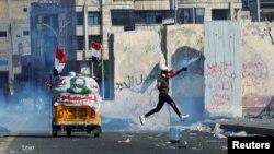 معترض بغدادی گاز اشکآور را به سوی نیروهای امنیتی پرتاب میکند