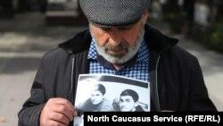 Муртазали Гасангусенов с фотографией убитых сыновей