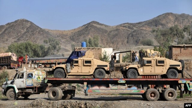 Pakistan -- Drivers stand beside a truck carring Humvee for NATO forces in Afghanistan parked at Torkham border crossing, 28Nov2011
