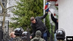 Volodymyr Parasyuk, a former Maidan activist and current lawmaker, tears away a Russian flag from the Russian Consulate during a rally in Lviv on March 9.