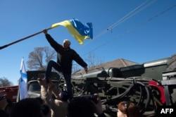 Пророссийский протестующий снимает украинский флаг во время штурма военной части в поселке Новофедоровка. 22 марта 2014 года