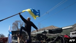 A pro-Russian protester takes down a Ukrainian flag as a group of some 200 protesters storm a Ukrainian air base in the small city of Novofedorivka in western Crimea on March 22.