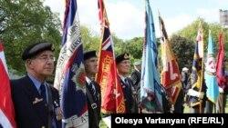 Под звуки оркестра за мемориалом в память погибших во Второй мировой войне ровным рядом выстроились пожилые британские ветераны со знаменами в руках. У нескольких на груди российский триколор