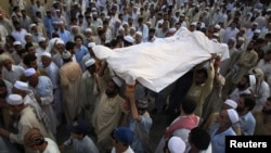 Residents carry the draped body of a suicide bomb victim to his grave in Pabbi, east of Peshawar, in July.