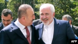 Turkish Foreign Minister Mevlut Cavusoglu, left, welcomes his Iranian counterpart Mohammad Javad Zarif for a meeting at the Foreign Ministry in Ankara on August 12.