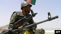 An Afghan soldier keeps watch at a checkpoint in Kandahar.