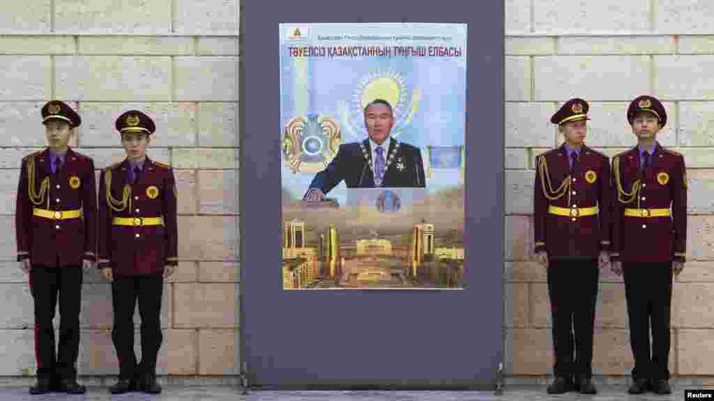 Military academy students stand next to a poster of President Nazarbaev at the opening of an exhibition to mark the inaugural Day of the First President in the Central National Museum in Almaty.