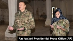 Azerbaijani President Ilham Aliyev and his wife, Vice President Mehriban Aliyeva, pray inside a mosque recaptured from ethnic Armenian forces during the 2020 conflict in Nagorno-Karabakh.