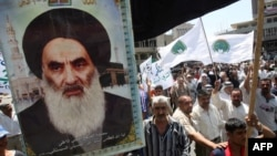 Shi'a carry a poster of Grand Ayatollah Ali al-Sistani as they rally outside the Al-Kholani Mosque in central Baghdad.