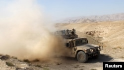 An Afghan security vehicle advances towards Kunduz city on September 30.